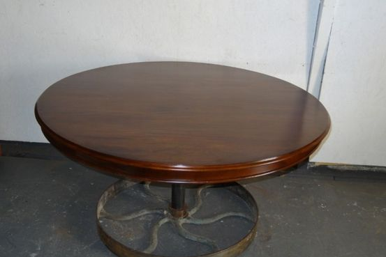 round mahogany table top sat over  antique iron wheel base Feature Image